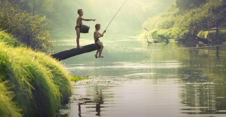 2drenge fisker med stang ved idyllisk flod